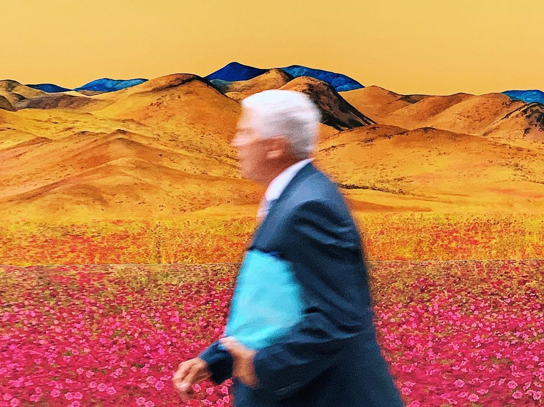 Man in suit walking in front of landscape painting installation
