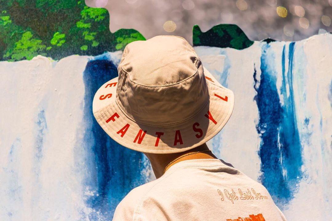 Back of hat-wearing person's head, in front of waterfall landscape art installation