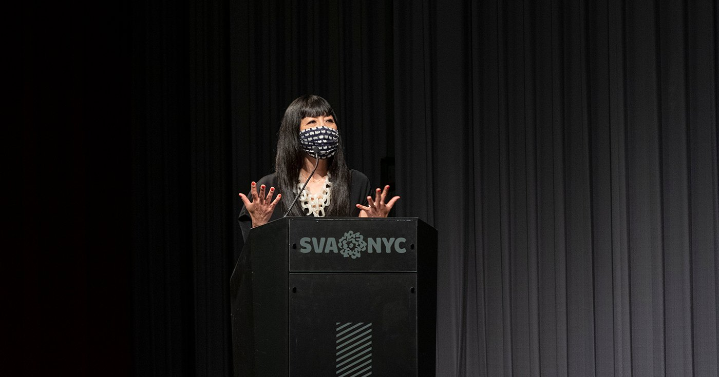 Miya Osaki giving the opening words to Thesis show 2021, she is behind a podium that reads SVA NYC