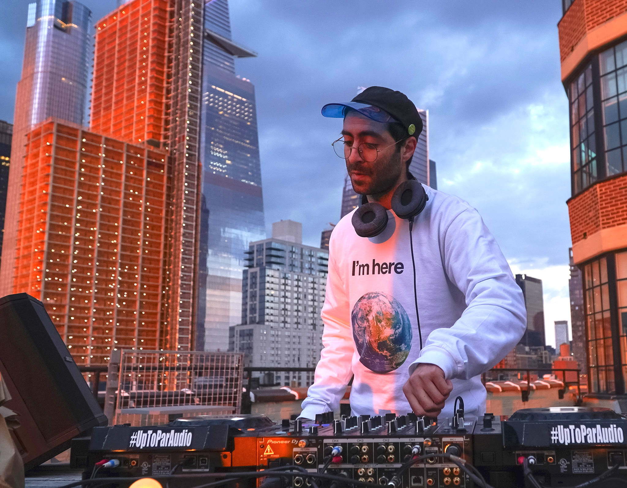 Amer Djing against the NYC skyline at golden hour.