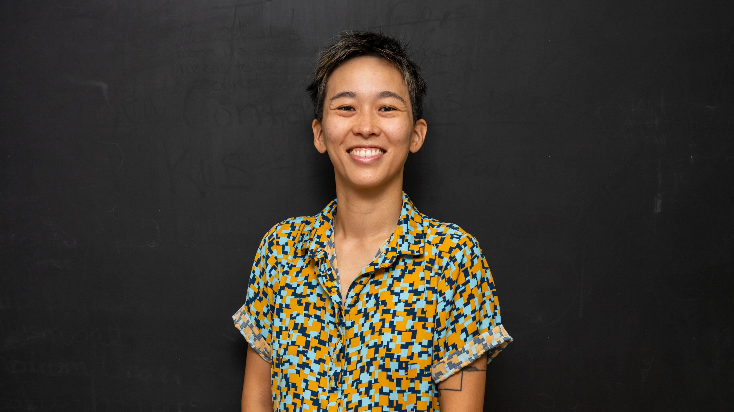 Stephanie Yim smiling for their photo wearing a colorful all overprint shirt.